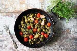 coles de Bruselas con verduras y hierbas en una sartén foto