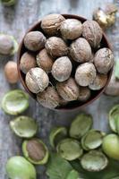 nueces en un bol. hojas de nuez nueces en una cáscara verde foto
