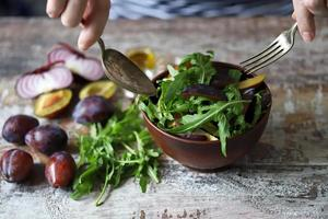 Healthy salad mix male hands with a spoon and fork. Arugula plum salad. photo