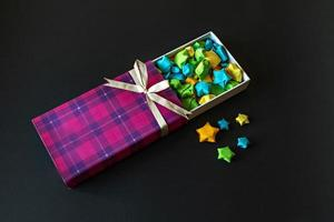 Colored gift box with satin bow with origami paper stars on black background. Gifts for the holidays. photo