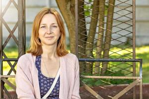Joven mujer europea sentada en un banco en el jardín.retrato de una niña sonriente y feliz foto