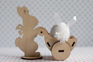 un conejo de madera lleva un carro con un huevo con orejas de conejo. decoraciones de pascua foto