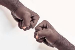 mano masculina apretada en un puño sobre un fondo blanco. un símbolo de la lucha por los derechos de los negros en américa. protesta contra el racismo. foto