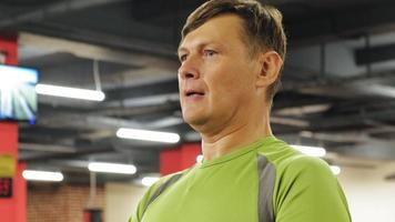 A overweight man lifts a barbell standing at the gym video