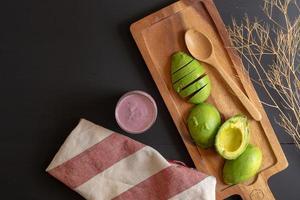 Aguacate orgánico fresco cortado por la mitad sobre una mesa de madera negra foto