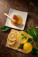 Lemon juice with honey on wooden table lemons and sage leaves photo