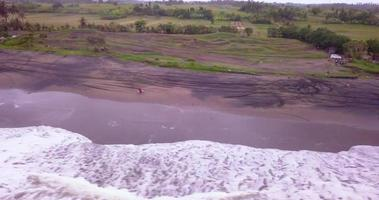 Aerial drone view of a man riding his motocross motorcycle on the beach. video