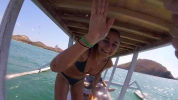 A girl in a bikini gives a high five and fist bump on a boat. video