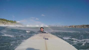 POV of a surfer duck diving under a wave while surfing on his surfboard. video