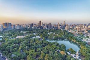 Lumphini Park and skyscrapers in Bangkok city, Thailand photo