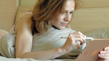 femme au lit à l'aide d'une tablette informatique matin video