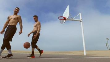 Two men play one-on-one basketball hoops on a beach court. video