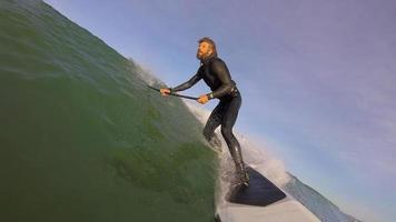 pov de un hombre sup stand up paddleboard surfeando en una ola. video