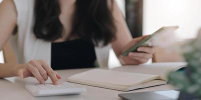 Cerrar empresario usando calculadora y teléfono inteligente para calaulating finanzas, impuestos, contabilidad, estadísticas y concepto de investigación analítica foto