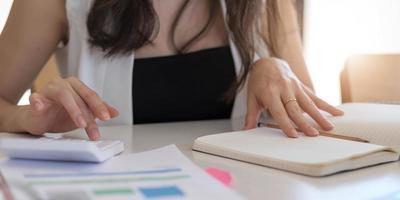 Hombre de negocios de cerca con calculadora y computadora portátil para calaulating finanzas, impuestos, contabilidad, estadísticas y concepto de investigación analítica foto
