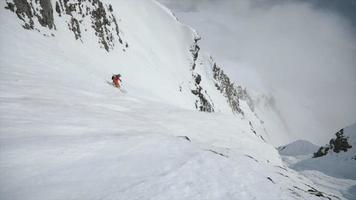een skiër die van een steile berg in de sneeuw skiet. video