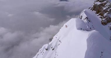 drone vanuit de lucht van een skiër die van een steile besneeuwde berg skiet. video