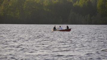 Young adults racing and rowing a boat on a lake at sunset. video