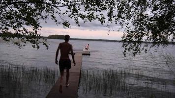 de jeunes adultes vont nager au bout d'un quai du lac. video