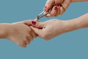 La mano de la mujer está utilizando un cortaúñas para cortar las uñas de un niño aislado sobre fondo de color azul pastel foto