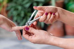 Primer plano una mano de mujer está utilizando un cortaúñas para cortar las uñas de los niños foto