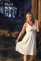 Countrywoman in a white summer long dress standing and posing in front of the old village barn. photo