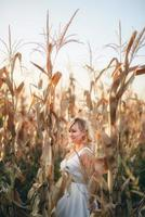 Woman in a white summer long dress walks on a cornfield and posing in sunset time. photo