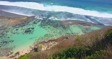 Aerial drone view of a coral reef and waves at the beach. video