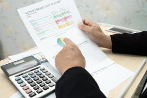 Contador asiático que trabaja y analiza la contabilidad del proyecto de los informes financieros con el gráfico y la calculadora en la oficina moderna, las finanzas y el concepto empresarial. foto