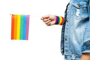 Señora asiática que sostiene la bandera del color del arco iris aislada en el fondo blanco, símbolo del mes del orgullo lgbt celebra anualmente en junio las redes sociales de los derechos humanos gay, lesbianas, bisexuales, transgénero. foto