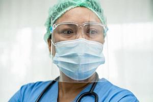 médico asiático con protector facial y traje de ppe nuevo normal para comprobar que el paciente protege la seguridad infección brote de coronavirus covid-19 en la sala de cuarentena del hospital de enfermería. foto
