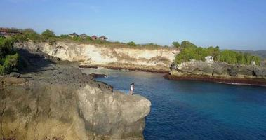 Aerial drone view of a young woman standing on a rocky cliff. video