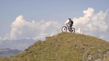Mountain biker biking to the top of a hill in the mountains. video