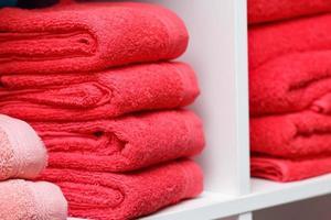 pocas toallas rojas en el estante blanco, salón de spa, tienda, textil de baño. foto