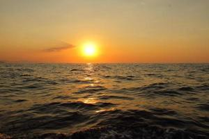 Orange bright sunset under the ocean. Sun reflection on water scenic, yellow dusk, peaceful nature landscape photo