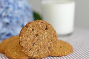 Oat cookies with glass of milk for breakfast on table cloth and blue flower on background, rustic healthy food photo