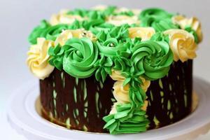 Precioso pastel casero cubierto de rosas amarillas y verdes hechas de crema de mantequilla, marco de chocolate, glaseado sobre fondo blanco. foto