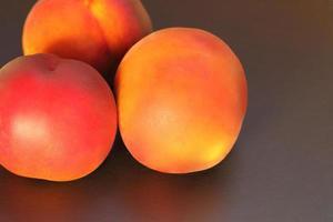 Ripe peach fruit, three peaches Prunus persica close-up on black background photo