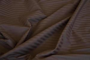 Wrinkled material with wrinkles, folds on fabric, fabric background. Linens. Brown with light stripes, blank photo