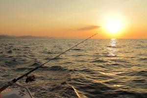 Fishing during sunset on ocean photo