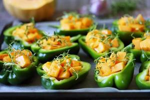 Green peppers stuffed with pumpkin pieces photo