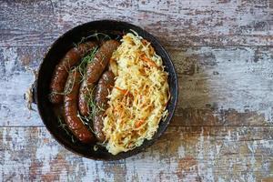 Bavarian sausages in a pan with stewed sauerkraut Oktoberfest food photo