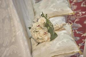 The double bouquet resting on white cushions photo