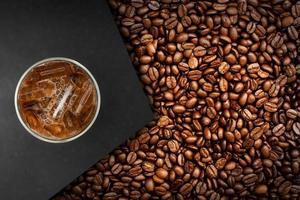 Cup of coffee with coffee beans on table photo