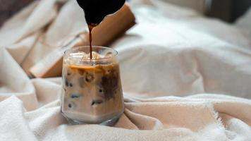 Barista pouring milk into a glass of iced coffee photo