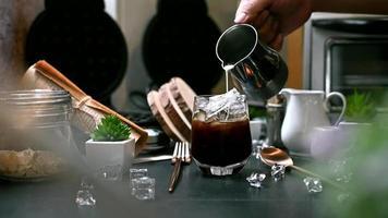 Barista gießt Milch in ein Glas Eiskaffee video