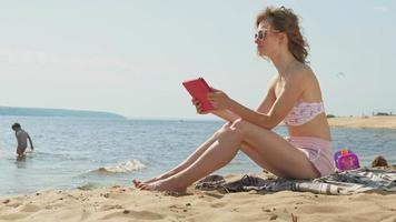 Young woman uses computer tablet on the beach river bank video