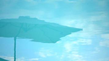 weerspiegeling van parasols in een blauw zwembad in een luxeresort in italië, europa. video