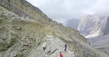 Aerial drone view of a man and woman couple hiking in the mountains. video