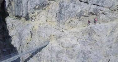 vista aérea de drone de una pareja de hombre y mujer caminando por un puente en las montañas. video